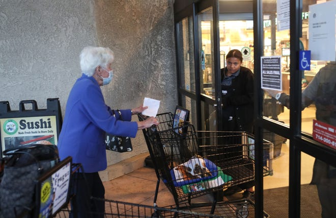 A woman enters Vons grocery store as they opened for the first two hours just for seniors as the coronavirus disrupts lives in Palm Springs, March 18, 2020.