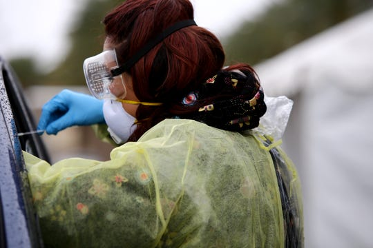 Medical staff from Riverside University Health collect nasal samples from members of the public that were referred for testing for the coronavirus at a drive-up site in Indian Wells, Calif., on Wednesday, March 18, 2020.