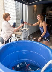 Bartender Jessi Dosen, right, sells crowlers to Macy Williams at Perfect Plain Brewing Co. in downtown Pensacola on Wednesday.