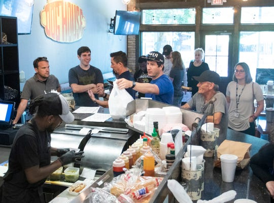 A line of people wait for take-out orders at the Dog House in downtown Pensacola on Wednesday, March 18, 2020.  Following recommended guidelines to help prevent the spread of Coronavirus, many restaurants are offering 50% capacity eat-in service as well as take-out and roadside pickup.