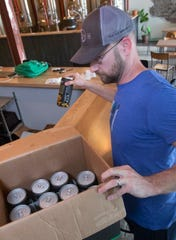 Lee Mason, of Ames, Iowa, packs a box with his to-go crowlers at Odd Colony Brewing Company in downtown Pensacola on Wednesday, March 18, 2020. The brewery is hoping that the sale of to-go crowlers will help make up for lost sales due to the impact of the coronavirus situation.