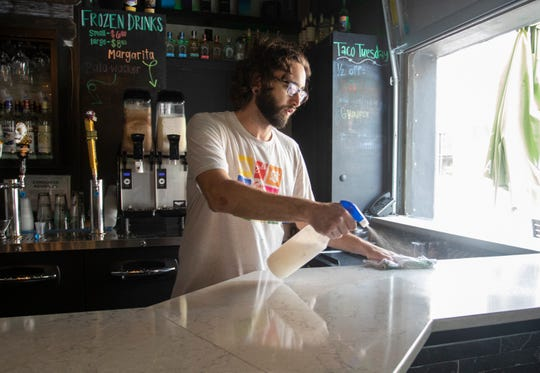 Bartender Nick Stearns cleans down the counter at Taco Agave in downtown Pensacola on Wednesday, March 18, 2020.  Following recommended guidelines to help prevent the spread of Coronavirus, many restaurants are offering 50% capacity eat-in service as well as take-out and roadside pickup.