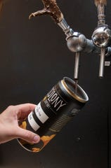 Blake Foster prepares a to-go crowler at Odd Colony Brewing Company in downtown Pensacola on Wednesday, March 18, 2020.  The brewery is hoping that the sale of to-go crowlers will help make up for lost sales due to the impact of the coronavirus situation.