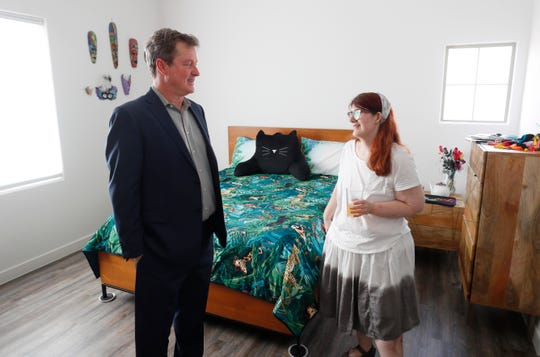 """Eric Gruber, co-founder and principal of Cadence Living at Luna Azul, receives a tour from Leah Mapstead at Luna Azul, a gated community for adults with disabilities in Phoenix, Ariz. on March 16, 2020. Mapstead's room was filled with animals and video game systems as Mapstead is a self-professed """"gamer."""""""