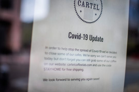A sign outside Cartel Coffee Lab in downtown Phoenix informs customers it has closed due to COVID-19 precautions on March 18, 2020. Phoenix Mayor Kate Gallego announced on Tuesday the city was declaring a state of emergency, closing bars and moving restaurants to takeout, delivery and drive-thru only starting at 8 p.m. Tuesday.