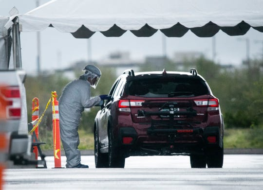 Individuals are tested for COVID-19 at a mobile clinic set up in the parking lot at the Mayo Clinic Hospital in Phoenix on the morning of March 18, 2020.