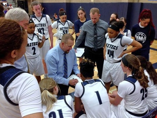 Pima women's basketball head coach Todd Holthaus designs a play for his team during a timeout in a game.