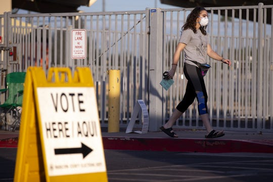 A woman walks with her ballot to vote in the Democratic presidential primary on March 17, 2020, at the Madison Park School polling location in Phoenix.
