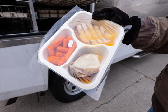 Senior Nutrition Program employee Trish Dancey retrieves a tray of food from the warm storage section  of their delivery truck Wednesday, March 18, 2020, while delivering meals in a Port Huron neighborhood.