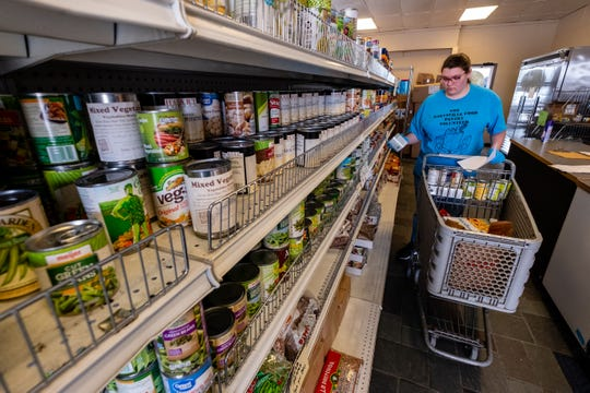 Volunteer Eyreana Warsinski, 17, fills a shopping cart Wednesday, March 18, 2020, at SOS Marysville Food Pantry. Normally visitors to the pantry are allowed in the store, but to help prevent the spread of coronavirus, they are being asked to wait in their vehicles.