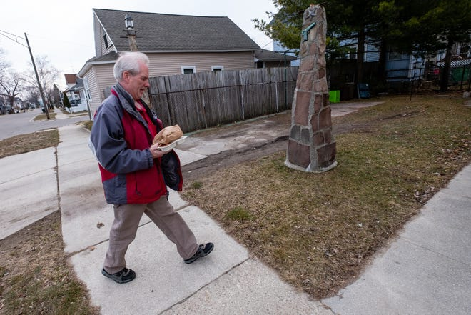 Senior Nutrition Program employee Ken Smith carries a meal up to a home Wednesday, March 18, 2020, while delivering meals in a Port Huron neighborhood. Smith, who's worked for the program for 18 years, said he's had two new clients tell him they signed up for home delivery due to the virus.