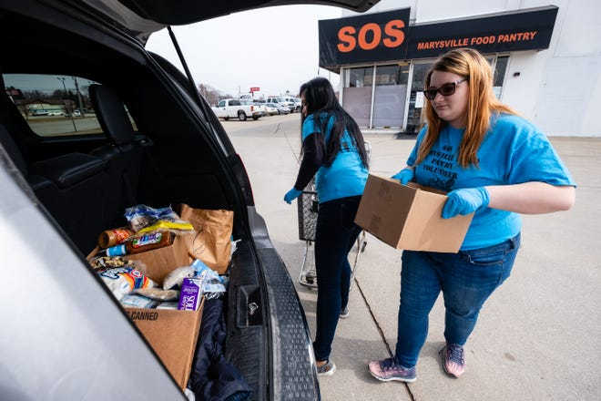 Director Carmela Burns, left, and volunteer Emily Ross, 16, load food into the back of a van Wednesday, March 18, 2020, at SOS Marysville Food Pantry. Normally visitors to the pantry are allowed in the store, but to help prevent the spread of coronavirus, they are being asked to wait in their vehicles.