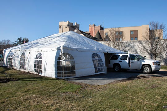 Workers set up a tent at St. Anthony's Hospital in Warwick, which will be used as a drive thru testing site for COVID-19.