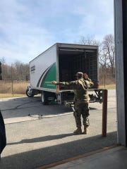 A member of the National Guard helps direct a truck to drop off supplies in Dutchess County as seen on Tuesday, March 18, 2020.