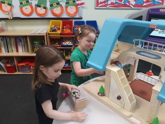 Ezmae Herring and Charli Kennedy play in the preschool room (left to right) with the dollhouse at Dreamland Daycare in Poughkeepsie on Tuesday, March 18, 2020.
