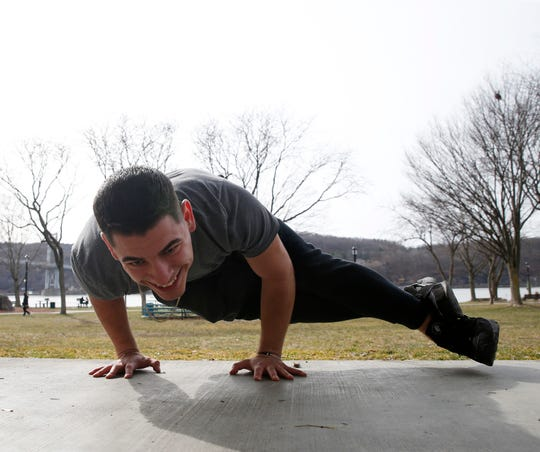 Seth Tasetano, a personal trainer who has been seeking alternatives to teaching in gyms, warms  before meeting a client at Waryas Park in the City of Poughkeepsie on March 18, 2020.