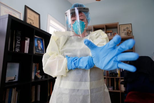 Christine MacNeil puts on supplies she would use to limit her exposure to an infectious disease such as coronavirus at her home in Pine Plains on March 18, 2020.  MacNeil is a registered nurse with the Dutchess County Medical Reserve Corps