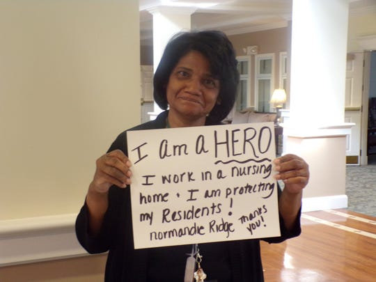 Normandie Ridge shares a photo on its Facebook page of a staff member holding a sign. Credit: Normandie Ridge Senior Living Community