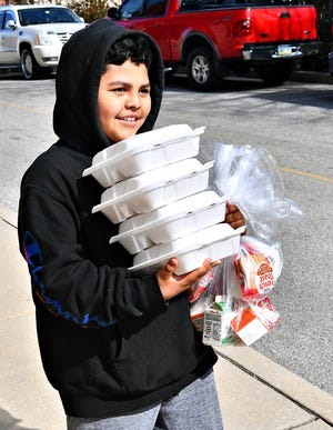 Lincoln Charter School fourth grader Leonel Valencia, 10, left, picks up lunch for four at Lincoln Charter School in York City, Wednesday, March 18, 2020. The school obtained a COVID-19 waiver which allows them to serve the meals not only to Lincoln charter students, but to all children on the west end between the ages of 2-18. Dawn J. Sagert photo