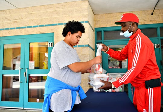 Lincoln Charter School Principal and CEO Leonard Hart, right, hands a stack of lunches to Jordan Mitchell, 17, of York City, at the school in York City, Wednesday, March 18, 2020. The school obtained a COVID-19 waiver which allows them to serve the meals not only to Lincoln charter students, but to all children on the west end between the ages of 2-18. Dawn J. Sagert photo