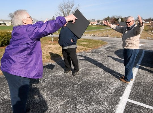 """The Rev. Lou Ann Jones, left, reaches out to member Lonnie Barnhart and says """"air-hug"""" before a prayer service for those impacted by the coronavirus pandemic in March. Beginning May 22, churches can hold services inside with certain limitations."""