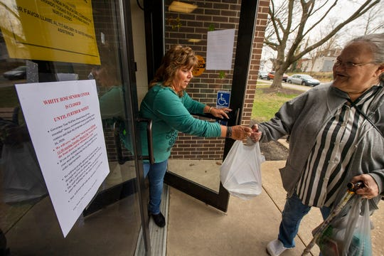 Lisa Krout, executive director for the White Rose Senior Center hands Sandra Ocasio a lunch after the center in York was closed as a social distancing measure for coronavirus.