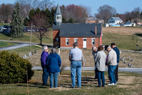A group of members gather to pray for those impacted by the Coronavirus pandemic. In the background is the church St. John's Blymire's United Church Of Christ near Dallastown, used exclusively prior to 1980.