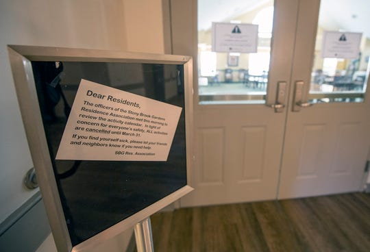 A social room at Stony Brook Gardens senior living complex has signs saying all activities are canceled.