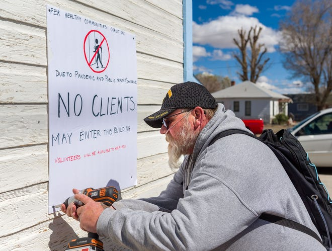 Yerington Food Bank Community Health Worker Ron Hoard posts a sign advising clients that they can no longer enter the food pantry due to coronavirus . Volunteers will be delivering food boxes to clients outside the building.