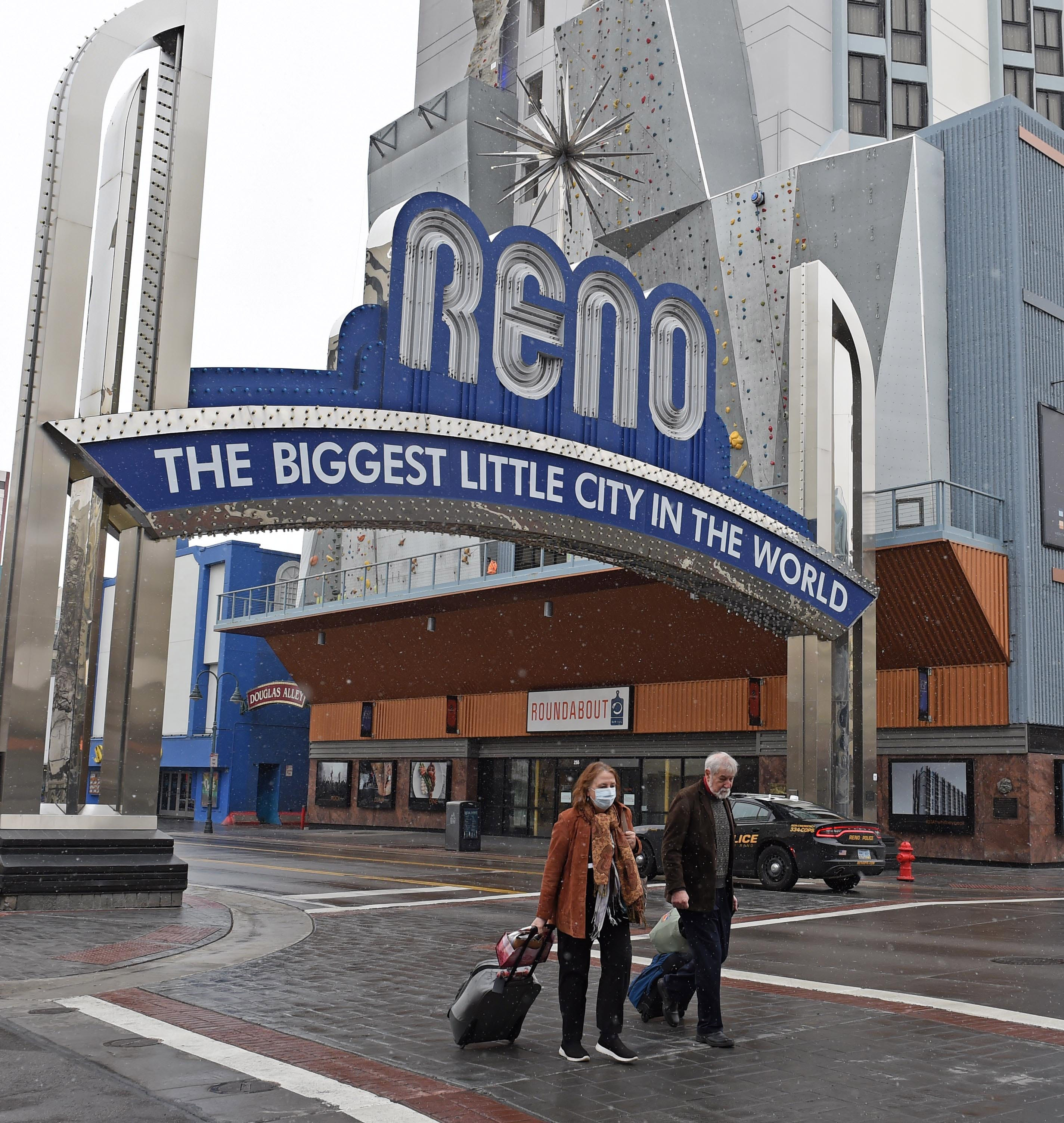 Ted and Chris Champman cross the street in downtown Reno on March 18, 2020. The couple, who is from Florida, was planning on staying in Reno two days, but they had to leave after their first night.