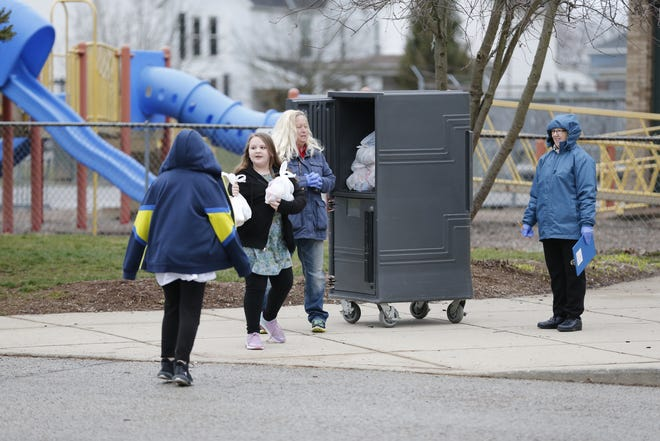 With schools abruptly closing because of COVID-19 and switching to virtual learning and home, school lunch programs switched to providing to-go meals for families that needed them. Here, Cindy McGraw and Nancy Backmeyer hand out meals to children at Vaile Elementary on Tuesday, March 17, 2020.