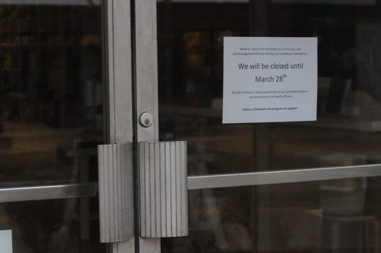 A notice in the window of Ply Fiber Arts on East Main Street notifies customers that the store will be closed until March 28.