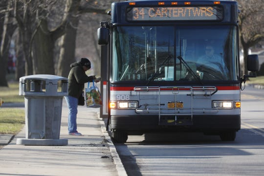 A commuter gets on a bus at a Carter Street bus stop on Wednesday, March 18, 2020.