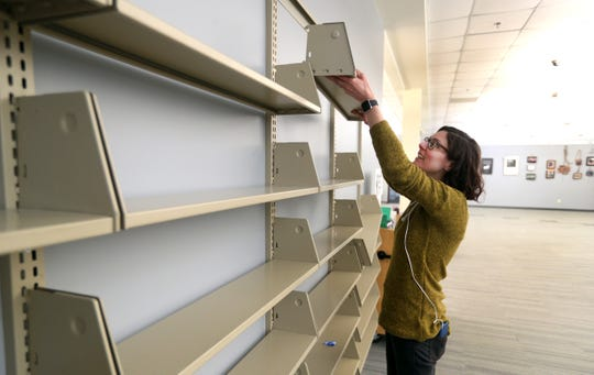 Colleen Hernandez replaces shelving after cleaning them at the Webster Public Library.  The library is closed to the public but books can be picked up curbside.