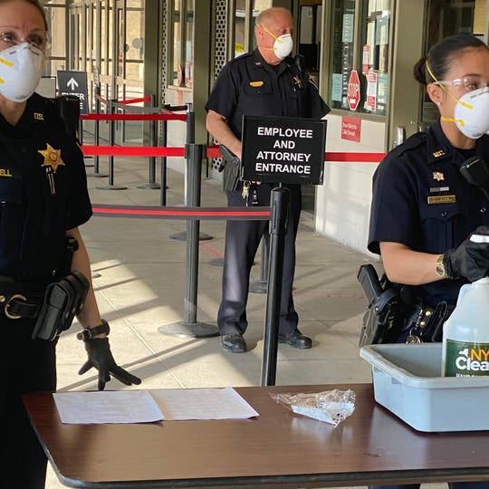 Court deputies adorned in masks and gloves at the entrance of the Monroe County Hall of Justice Wednesday morning.