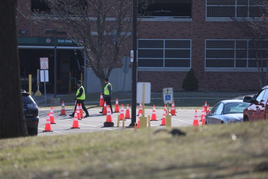 Cones are moved around the  Wilson Health Center parking lot for people who were referred to the drive through COVID-19 testing site on Wednesday, March 18, 2020.