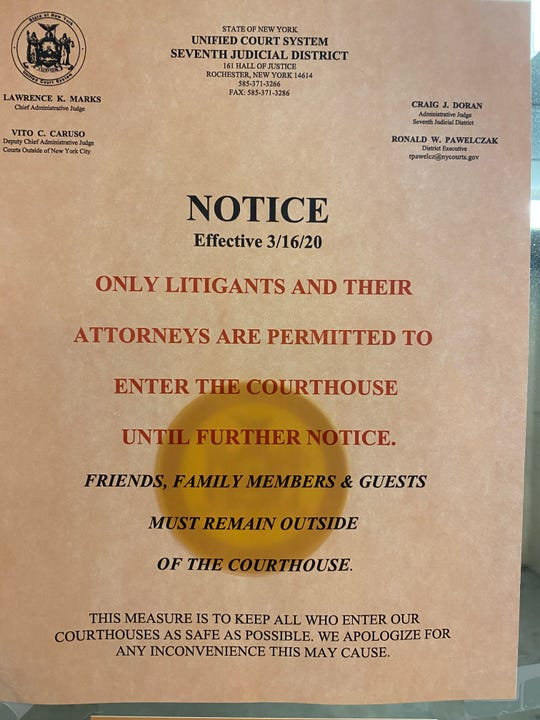 """Only litigants and their attorneys are permitted to enter the courthouse until further notice,"" a posted sign states at the Monroe County Hall of Justice on Wednesday."