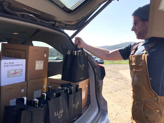 Mason Carroll loads a wine delivery at Illahe Vineyards in Dallas on March 18, 2020. The winery has started delivering orders of wine to local residents in response to Gov. Kate Brown's mandate to close bars, restaurants and tasting rooms.