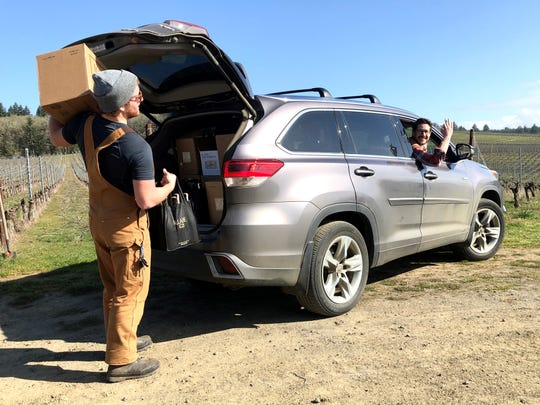 Mason Carroll loads a wine delivery and Christopher CAnele-Parola waves, at Illahe Vineyards in Dallas on March 18, 2020. The winery has started delivering orders of wine to local residents in response to Gov. Kate Brown's mandate to close bars, restaurants and tasting rooms.