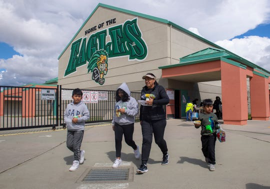 A family gets breakfast and lunch at the Cesar E. Chavez Elementary School on Tuesday, March 17, 2020.