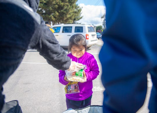 A young girl receives a hot meal on Tuesday, March 17, 2020.