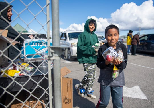 Two Alisal Community School students receive a grab and go meal on Tuesday, March 17, 2020.