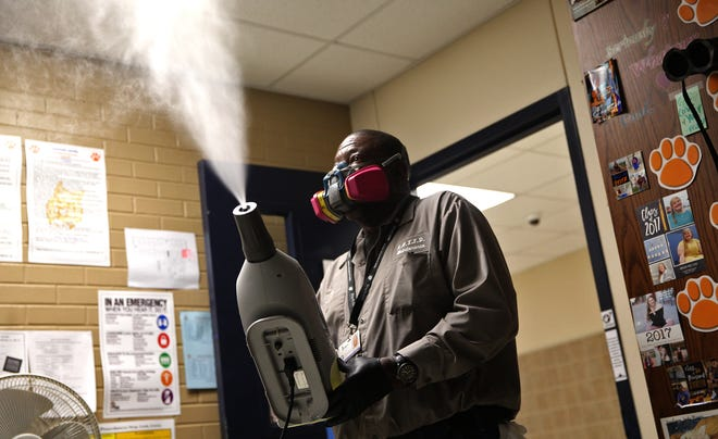Ira Routt sprays disinfectant in a class room at Central High School on Wednesday, March 18, 2020 as part of a district wide effort to prevent coronavirus.
