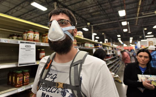 Bastrop resident Bryan Crigger, who said he and his family recently left China amid the novel coronavirus pandemic, wears a protective mask while shopping at H-E-B on Sunday in Bastrop.
