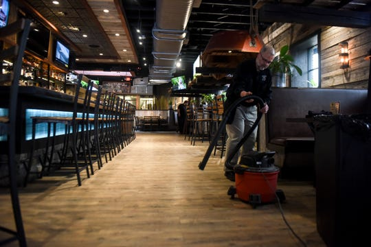 Assistant manager Tim Sanstead cleans an empty restaurant on Wednesday, March 18, 2020 at MacKenzie River. The restaurant is taking only to-go orders due to the coronavirus restrictions.