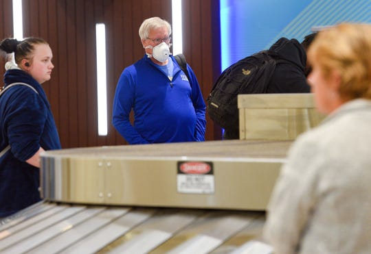 A traveler wearing a mask waits for his luggage on Wednesday, March 18, at the Sioux Falls Regional Airport.