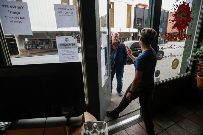 Randy Harwood, left, a daily customer at the Mudhouse, orders a black coffee from Jonathan Stratman on Wednesday, March 18, 2020. The downtown business was taking orders for carryout only due to the coronavirus and a city order that bars and restaurants temporarily close their dining rooms.