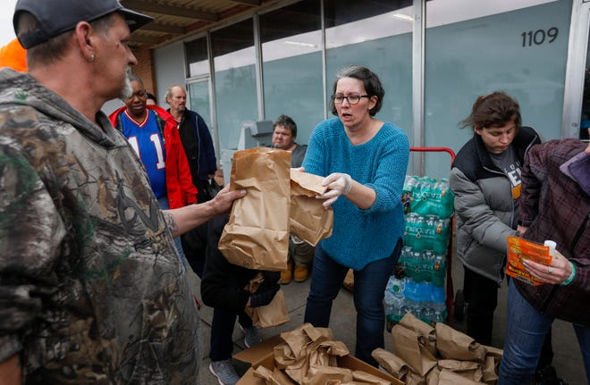 Christie Love, center, hands out sandwiches to the homeless at the Connecting Grounds on Tuesday, March 17, 2020.