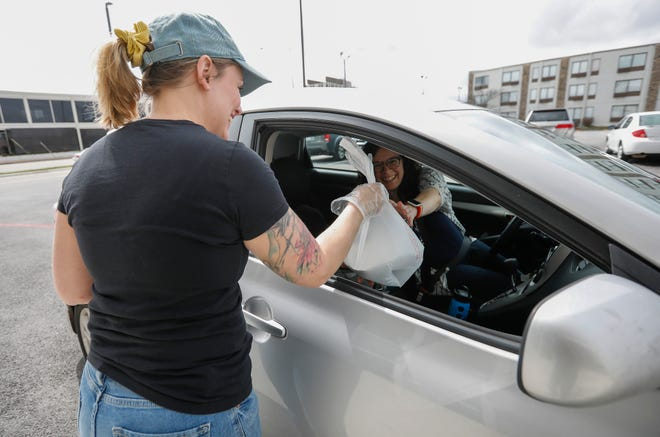 Melissa Smallwood, of The Wheelhouse in Springfield, delivers a to-go order to a customer on March 18, 2020. Gov. Mike Parson signed both protections for businesses against COVID lawsuits and a permanent extension of to-go cocktail sales Wednesday.