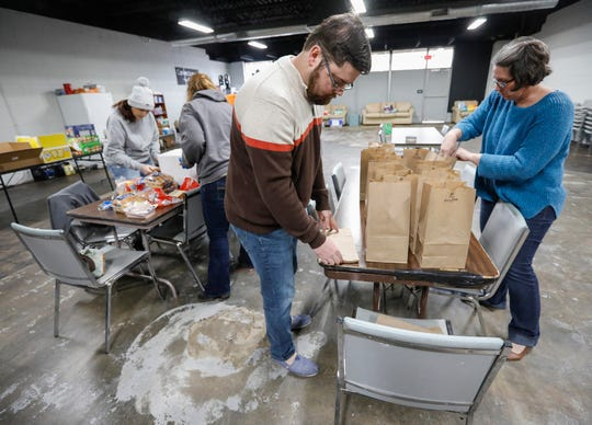 Christie Love, right, and Scott Madden set out paper bags so they can be filled with sandwiches to hand out to the homeless at the Connecting Grounds on Tuesday, March 17, 2020.